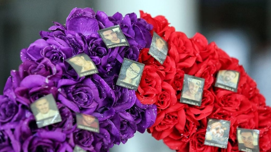 A heart-shaped wreath bears the 49 photos of the victims from the Pulse nightclub massacre, in the atrium of Orlando City Hall, Thursday, Aug. 4, 2016. The wreath was placed at city hall to raise continued awareness for the OneOrlando fund, to benefit the victims of the shootings and their families. (Joe Burbank/Orlando Sentinel via AP)