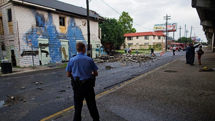 A New Orleans Police officer stands next to a partially collapsed building on the corner of North Claiborne Avenue and Ursulines Avenue after heavy rains and powerful winds hit in New Orleans, La., Thursday, Aug. 4, 2016. A brief but intense storm pummeled New Orleans on Thursday afternoon, toppling trees and power lines and collapsing at least two abandoned houses. (AP Photo/Max Becherer)