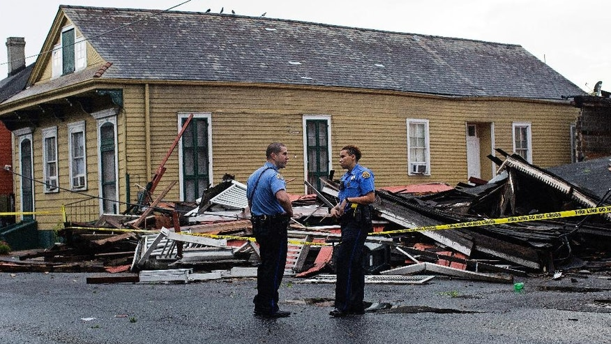 New Orleans Police officers stand in front of a collapsed building on the corner of North Claiborne Avenue and St. Philip Street after heavy rains and powerful winds hit in New Orleans, La., Thursday, Aug. 4, 2016. A brief but intense storm pummeled New Orleans on Thursday afternoon, toppling trees and power lines and collapsing at least two abandoned houses. (AP Photo/Max Becherer)