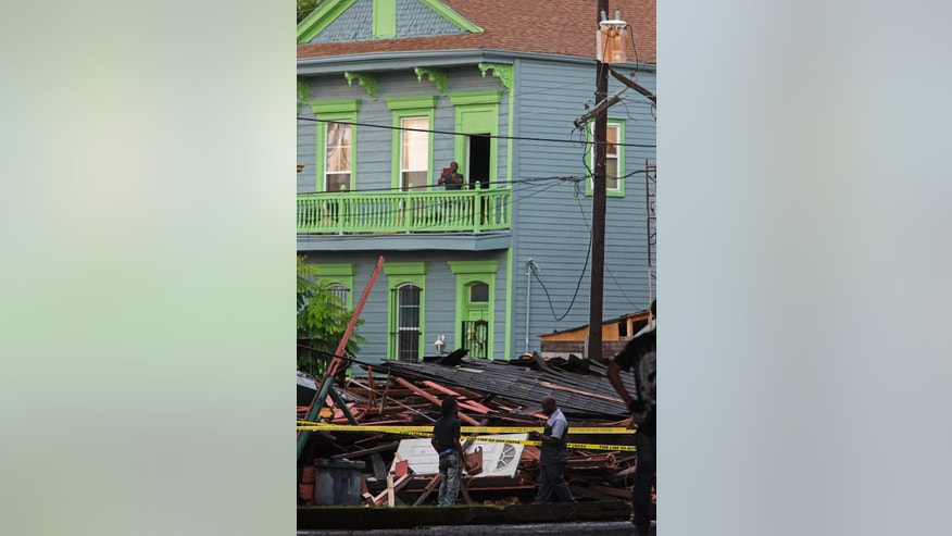 Bystanders inspect a collapsed building on the corner of North Claiborne Ave. and St. Philip Street after heavy rains and powerful winds hit in New Orleans, La., Thursday, Aug. 4, 2016. A brief but intense storm pummeled New Orleans on Thursday afternoon, toppling trees and power lines and collapsing at least two abandoned houses. (AP Photo/Max Becherer)