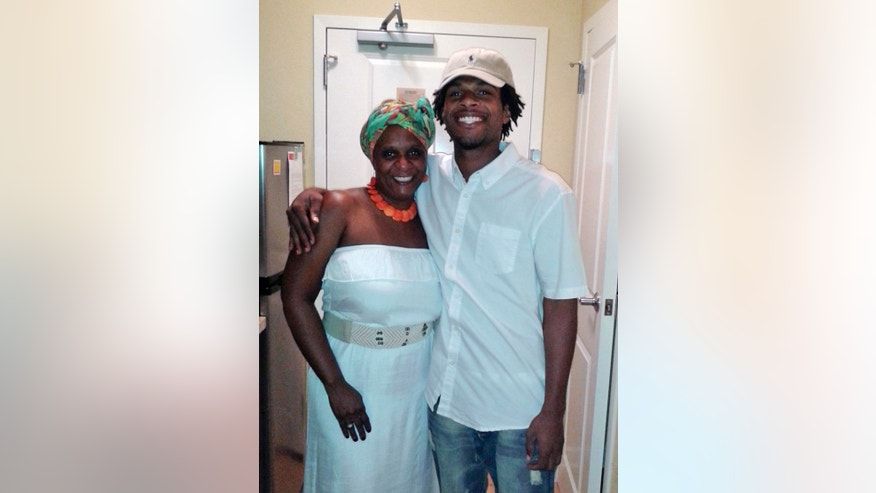 FILE - This undated file photo provided by the family of John Crawford III shows Crawford, right, with his mother Tressa Sherrod. Two years after a white policeman fatally shot John Crawford III on Aug. 5, 2014, in a Wal-Mart store in the Dayton suburb of Beavercreek, Ohio, as Crawford carried an air rifle picked up from a store shelf, the U.S. Justice Department has yet to conclude its investigation and won't say why, despite the family's push for an update. (Courtesy Family of John Crawford III via AP, File)