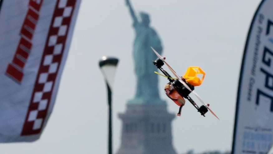 A pilot flies a small racing drone through an obstacle course on Governors Island, a former military installation in New York Harbor, Friday, Aug. 5, 2016. Drone pilots are gathering in New York City to compete in the National Drone Racing Championship. (AP Photo/Richard Drew)
