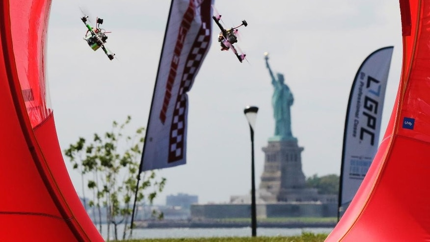 Pilots fly their small racing drones through an obstacle course on Governors Island, a former military installation in New York Harbor, Friday, Aug. 5, 2016. Drone pilots are gathering in New York City to compete in the National Drone Racing Championship. (AP Photo/Richard Drew)