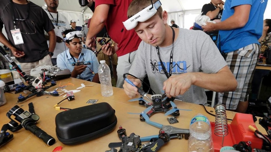 Competitor Tyler Brennan, a 22-year-old Air Force lieutenant from Colorado Springs, Colo., works on a quad copter before flying his racing drone through the obstacle course on Governors Island, a former military installation in New York Harbor, Friday, Aug. 5, 2016. Drone pilots are gathering in New York City to compete in the National Drone Racing Championship. (AP Photo/Richard Drew)