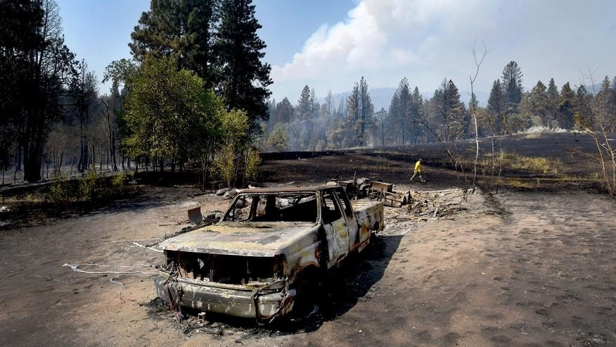 "Tod McKay, spokesman for the Bitterroot National Forest, walks by a burned truck and shop at Dave Campbell's home in Judd Creek Hollow, Tuesday morning, Aug. 2, 2016, in Hamilton, Mont. Both were burned by a wildfire fire that blew up Sunday near Hamilton, however, his house survived the fire. ""We're just trying to get people out of the way now,"" McKay told the Missoulian newspaper. ""We can rebuild homes. We need to get people out of this area."" (Kurt Wilson/The Missoulian via AP)"