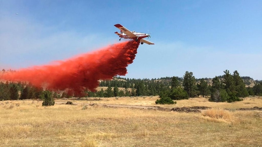 This photo, provided by the Montana Department of Natural Resources and Conversation, shows a plane dropping fire retardant on a fire line at the North Tullock wildfire near Hardin, Mont., Tuesday, Aug. 2, 2016. (Montana Department of Natural Resources and Conversation via AP)