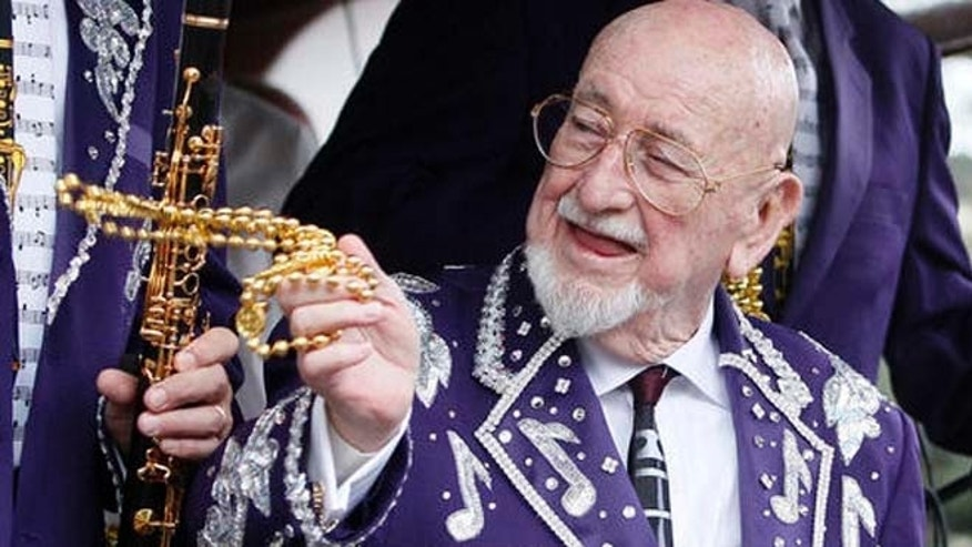 Musician Pete Fountain tosses beads to a reveler from a float as his Half-Fast Walking Club marches down St. Charles Avenue in New Orleans on Mardi Gras Day 2011. (AP Photo/Patrick Semansky)
