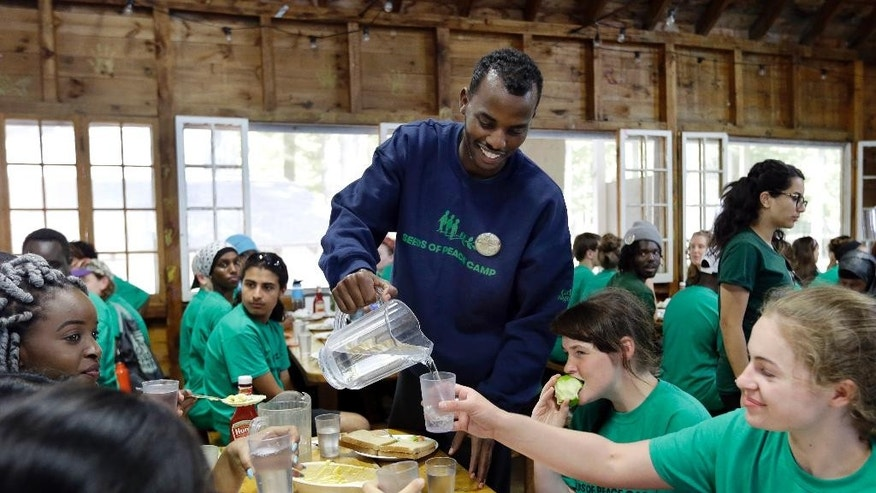 In this Aug. 4, 2016 photo, Somali-born Salat Ali pours water for his group of campers at the Seeds of Peace camp in Otisfield, Maine. Ali learned upon his arrival in Syracuse, N.Y. from a refugee camp at 11 that things weren't going to be perfect. He lived in a poor neighborhood, and others constantly picked fights with him. But he found his voice at Seeds of Peace, and he's returned as a counselor. (AP Photo/Elise Amendola)