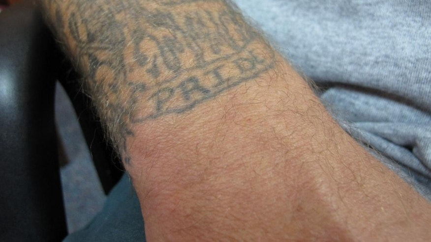 """A prison tattoo with the word """"PRIDE"""" stands out from Johnny Small's forearm during an interview at New Hanover Correctional Center in Wilmington, N.C., on Thursday, Aug. 4, 2016. Small is awaiting a hearing on whether his conviction in the 1988 murder of fish store owner Pam Dreher will be overturned. A hearing is scheduled to begin Monday, Aug. 8 for Small, who has always maintained his innocence. The judge could vacate the conviction, order a new trial or uphold the conviction.  (AP Photo/Allen G. Breed)"""