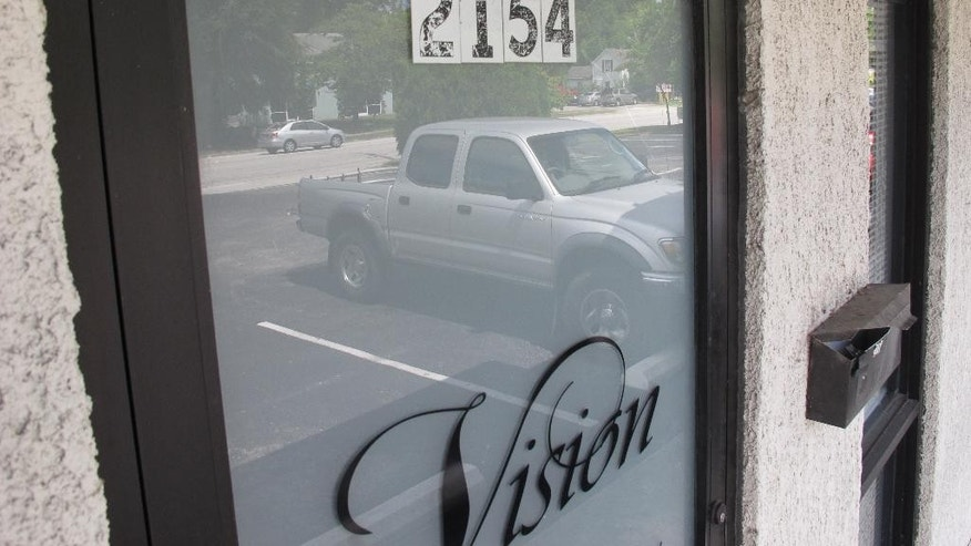 Cars are reflected in the door of the hair extensions store that occupies the former site of Tropical Paradise fish shop in Wilmington, N.C., on Thursday, Aug. 4, 2016. Fish store owner Pam Dreher was shot to death there in July 1988, but the man convicted of her murder is seeking to have the verdict overturned.  Johnny Small has been in prison since he was 16 for the murder he insists he didn't commit. A hearing is scheduled to begin Monday, Aug. 8 for Small, who has always maintained his innocence. The judge could vacate the conviction, order a new trial or uphold the conviction. (AP Photo/Allen G. Breed)