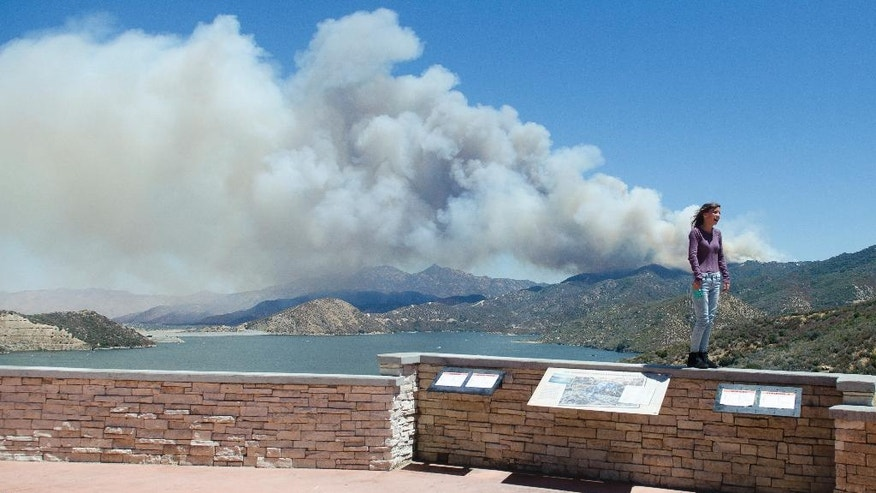 A wildfire burns in the background behind a sightseer as smoke billows over Silverwood Lake on Sunday afternoon, Aug. 7, 2016, in Crestline, Calif. A rapidly growing forest fire in Southern California is burning about 55 miles east of Los Angeles in a remote area near Silverwood Lake, a state recreation area, near the small mountain community of Crestline. A massive plume of smoke could be seen blowing north toward the Mojave Desert. (James Quigg/The Daily Press via AP)