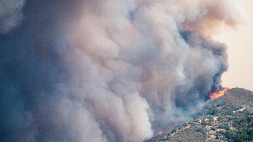A wildfire burns over a ridge towards Summit Valley, Calif., Sunday afternoon, Aug. 7, 2016. A rapidly growing forest fire in Southern California has prompted the evacuation of several dozen homes. A spokeswoman for the San Bernardino National Forest says residents in the sparsely populated Summit Valley area were ordered to leave their homes Sunday afternoon.  (James Quigg/The Daily Press via AP)