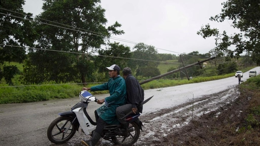 Power lines collapsed by Hurricane Earl hinder traffic flow on the road from Flores, in the northern Guatemalan border state with Belize, Thursday, Aug. 4, 2016. Earl deteriorated to a weak tropical storm Thursday as it passed over northern Guatemala en route to southern Mexico. (AP Photo/Luis Soto)