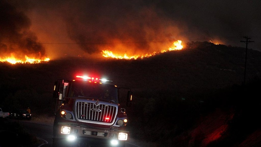 A fire engine drives away from flames on the ridge, east of Silverwood Lake in Crestline, Calif., Sunday, Aug 7, 2016. (Terry Peirson/The Press-Enterprise via AP)