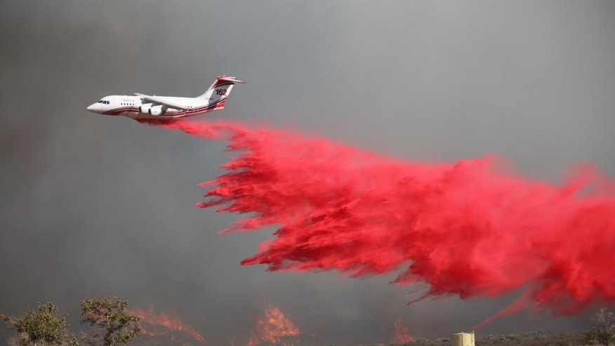 A tanker drops retardant on a wildfire fire east of Silverwood Lake Sunday, Aug. 7, 2016, in Crestline, Calif. Firefighters are battling a wildfire in Southern California that grew to more than 2 square miles in mere hours and forced the evacuation of homes near a reservoir. The fire is burning about 55 miles east of Los Angeles in a remote area near Silverwood Lake, a state recreation area, near the small mountain community of Crestline. (John M. Blodgett /The Inland Valley Daily Bulletin via AP)