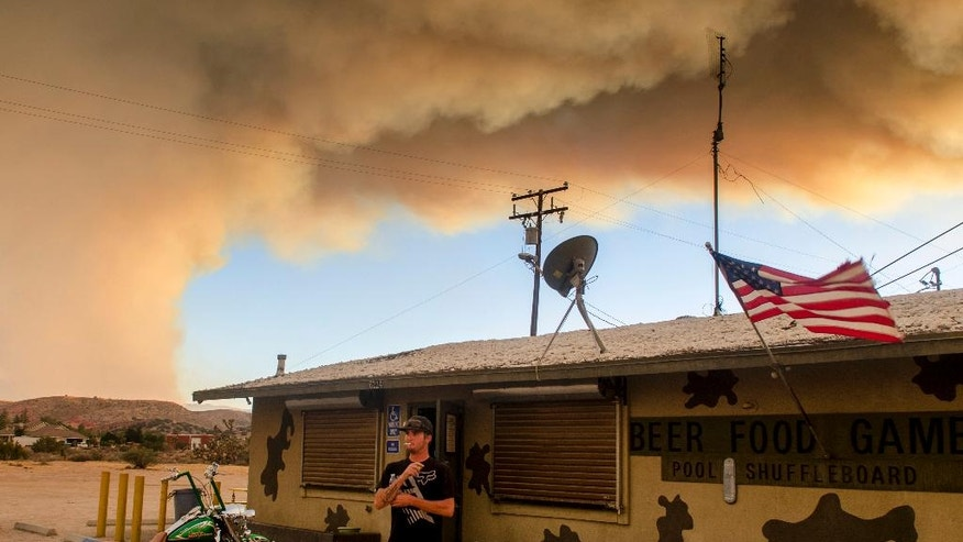 Trevor Rainwater watches a wildfire burn into Summit Valley from the Joshua Inn which was evacuated moments later Sunday, Aug. 7, 2016, in Hesperia Calif. Firefighters are battling a wildfire in Southern California that grew to more than 2 square miles in mere hours and forced the evacuation of homes near a reservoir. The fire, which broke out Sunday afternoon in the San Bernardino National Forest, prompted the evacuation order of the sparsely populated Summit Valley area east of the dam. (James Quigg/The Daily Press via AP)