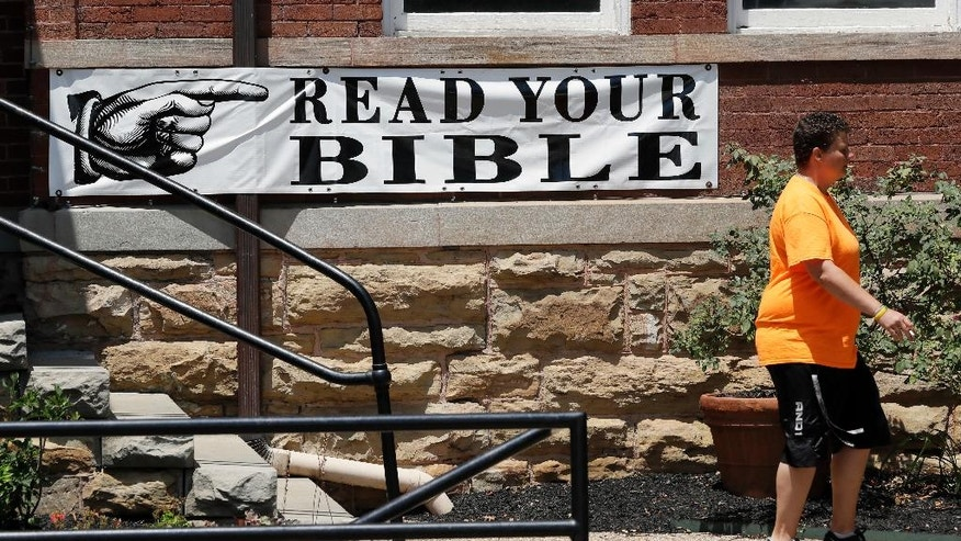 """In this July 23, 2016 photo, a woman walks by a sign hanging on the Rhea County Courthouse in Dayton, Tenn. The sign is a replica of one that was displayed during the 1925 Scopes """"monkey trial,"""" and is placed on the courthouse during the annual Scopes Festival. (AP Photo/Mark Humphrey)"""