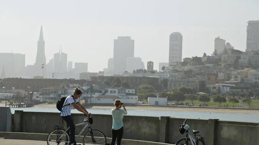 """FILE - In this Aug. 17, 2015 file photo, a couple on rental bicycles stop to take pictures at Aquatic Park of the hazy skyline in San Francisco. A 20-year-old man was shot to death while playing """"Pokemon Go"""" at a tourist attraction along San Francisco's waterfront, authorities and a family friend said on Sunday. Calvin Riley was shot Saturday night, Aug. 6, 2016, by an unknown assailant at Aquatic Park near Ghiradelli Square, the U.S. Park Police said. (AP Photo/Eric Risberg, File)"""