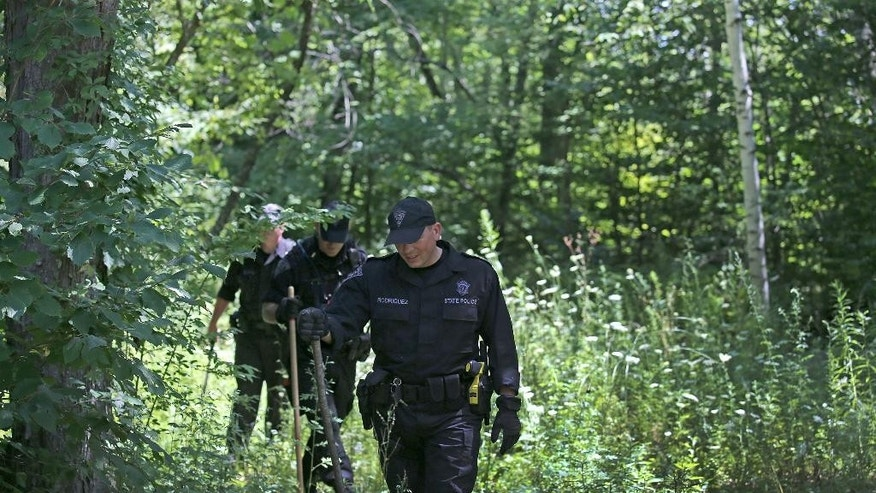 State Police search the woods for evidence after a woman visiting her mother was found slain, Tuesday, Aug. 9, 2016 in Princeton, Mass.   Police found the body of Vanessa Marcotte on Sunday night about a half-mile from her mother's home in Princeton, Worcester District Attorney Joseph Early Jr. said. She was visiting from New York City and was reported missing Sunday after she didn't return home.  (David L. Ryan/The Boston Globe via AP)