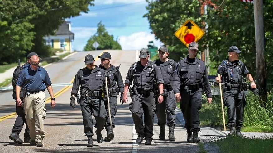 State Police walk down the street after searching through the woods for evidence after a woman visiting her mother was found slain, Tuesday, Aug. 9, 2016 in Princeton, Mass.   Police found the body of Vanessa Marcotte on Sunday night about a half-mile from her mother's home, Worcester District Attorney Joseph Early Jr. said. She was visiting from New York City and was reported missing Sunday after she didn't return home.  (David L. Ryan/The Boston Globe via AP)