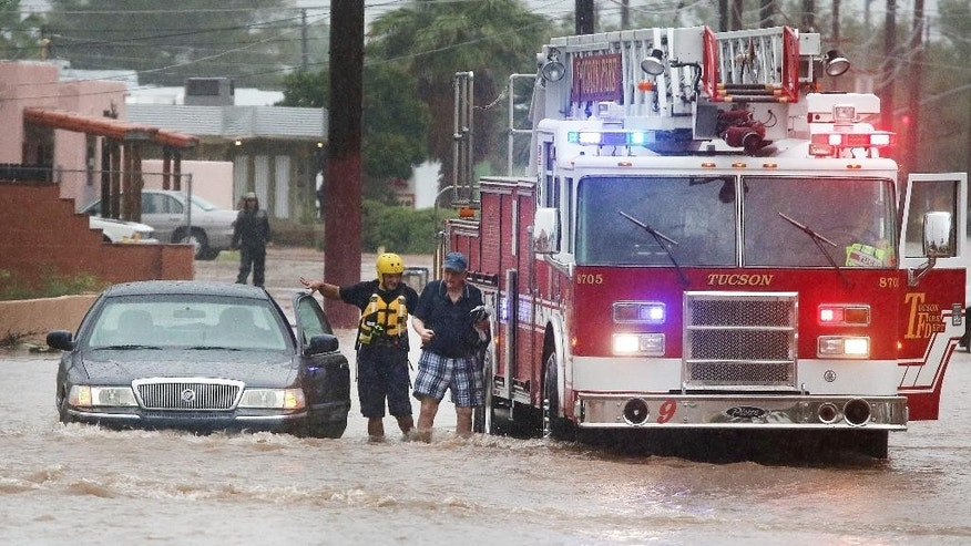 Tucson firefighters with Ladder 9 attend to a stranded motorist as heavy rains flood the intersection of North Country Club Road and East Seneca Street, Tuesday, Aug. 9, 2016, in Tucson, Ariz. Heavy rain associated with Tropical Storm Javier in Mexico fell over the American Southwest. (Mike Christy/Arizona Daily Star via AP)