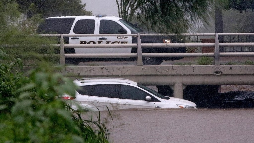A Tucson Police  vehicle drives by a partially submerged car that tried to cross a wash near Fort Lowell and Oracle as heavy rains flooded the area Tuesday, Aug. 9, 2016, in Tucson, Ariz. Heavy rain associated with Tropical Storm Javier in Mexico fell over the American Southwest.  (A.E. Araiza/Arizona Daily Star via AP)