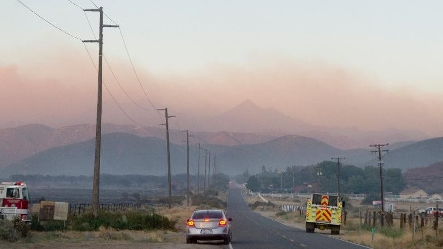 A wildfire burns in late evening Monday, Aug. 8, 2016, in Hesperia Calif. Smoke plumes roiling from flaming ridges of the San Bernardino Mountains blew all the way across the Mojave Desert to Las Vegas as California's latest big wildfire chewed through timber and brush Monday. Hundreds of firefighters, aided by 16 aircraft, battled flames that spread across 7 square miles on the northern side of the rugged mountain range about 60 miles east of Los Angeles. (James Quigg/The Daily Press via AP)