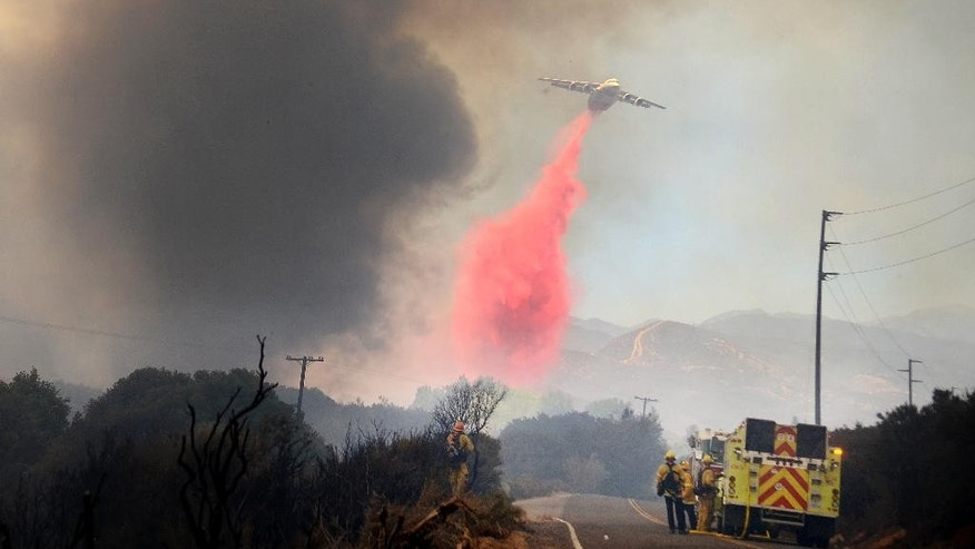 A jet tanker drops retardant on a wildfire along Highway 173 in Hesperia, Calif. on Monday, Aug. 8, 2016. Smoke plumes roiling from flaming ridges of the San Bernardino Mountains blew all the way across the Mojave Desert to Las Vegas as California's latest big wildfire chewed through timber and brush Monday. Hundreds of firefighters, aided by 16 aircraft, battled flames that spread across 7 square miles on the northern side of the rugged mountain range about 60 miles east of Los Angeles. (James Quigg/The Daily Press via AP)