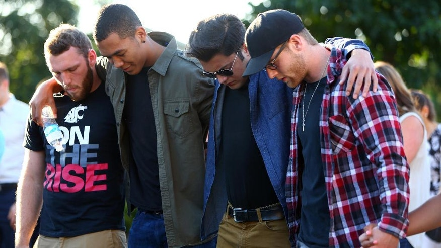 FILE--In this July 31, 2016, file photo, friends of victims huddle together during a prayer as hundreds gather for a community vigil for the victims of a shooting at a house party, killing three teenagers and wounding one. Young people attending the party where a gunman opened fire frantically told a dispatcher their friends were bleeding to death according to newly released tapes of the calls Tuesday, Aug. 9, 2016. (Genna Martin/seattlepi.com via AP, file)
