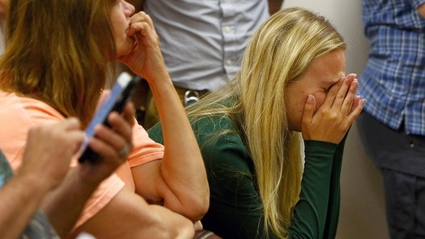 FILE--In this Aug. 1, 2016, file photo, a friend of the Mukilteo shooting victims reacts as Allen Ivanov appears at Snohomish District Court in Everett, Wash., via video link from the Snohomish County Jail. Young people attending the party where a gunman opened fire frantically told a dispatcher their friends were bleeding to death according to newly released tapes of the calls Tuesday, Aug. 9, 2016. (Genna Martin/seattlepi.com via AP, file)