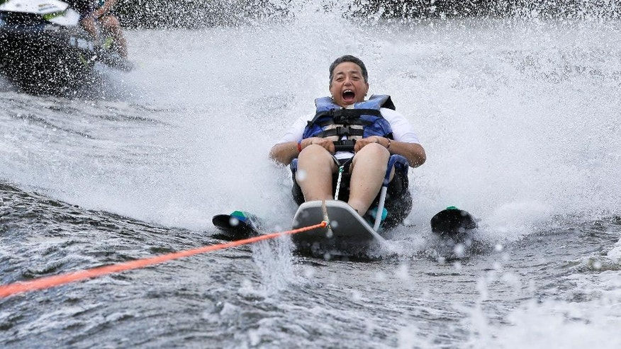 In this Tuesday, July 19, 2016 photo U.S. Navy veteran Raquel Ardin, of North Hartland, Vt., who suffered a broken neck while serving in the Navy, water skis during a rehabilitation clinic in Coventry, R.I. The Providence VA Medical Center hosted the four-day clinic for veterans with spinal cord injuries, amputations, visual impairments, neurological problems and other disabilities where they were able to go water skiing, kayaking, and sailing. (AP Photo/Steven Senne)