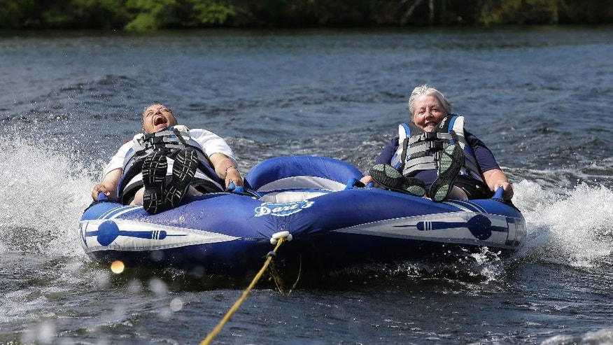 In this Tuesday, July 19, 2016 photo U.S. Navy veteran Raquel Ardin, of North Hartland, Vt., left, who suffered a broken neck while serving in the Navy, laughs while riding an inflatable craft with her partner Lynda Deforge, right, also of North Hartland, during a rehabilitation clinic in Coventry, R.I. The Providence VA Medical Center hosted the four-day clinic for veterans with spinal cord injuries, amputations, visual impairments, neurological problems and other disabilities where they were able to go water skiing, kayaking, and sailing. (AP Photo/Steven Senne)