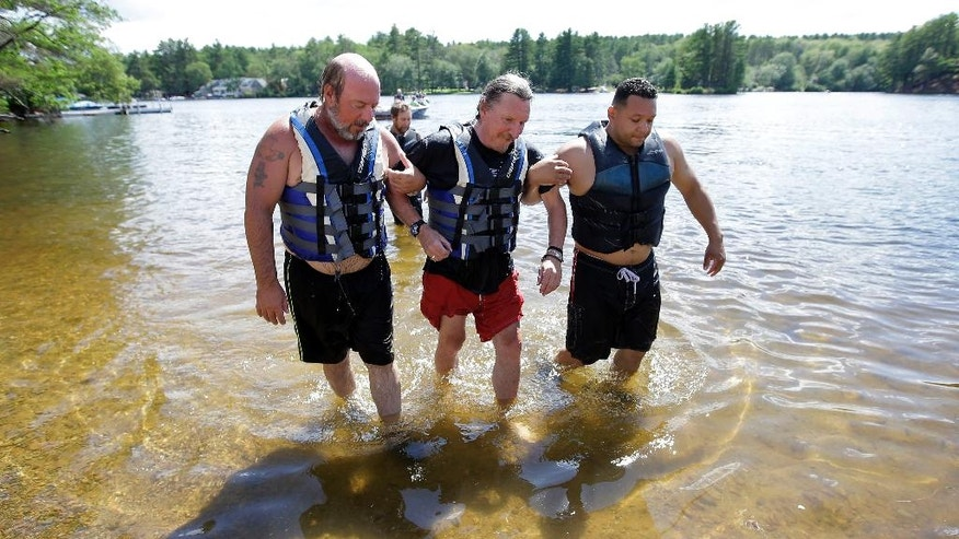 In this Tuesday, July 19, 2016 photo U.S. Army Vietnam War combat veteran William Long, 65, of New Haven, Conn., center, is escorted from the water by volunteers after water skiing during an adapted sports program for veterans, in Coventry, R.I. Long, who lives with Parkinson's disease, was exposed to the herbicide Agent Orange while serving in Vietnam. The Providence VA Medical Center hosted the four-day clinic for veterans with spinal cord injuries, amputations, visual impairments, neurological problems and other disabilities where they were able to go water skiing, kayaking, and sailing. (AP Photo/Steven Senne)