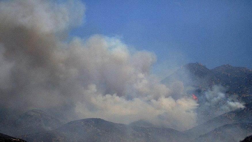 Flames from a wildfire rise up a ridge in Hesperia, Calif., Tuesday. Aug. 9, 2016. Mandatory and voluntary evacuations covered 5,300 homes in the Southern California fire area between mountain communities around Lake Arrowhead and the high desert city of Hesperia to the north, said Lyn Sieliet, a U.S. Forest Service spokeswoman. (James Quigg/The Daily Press via AP)