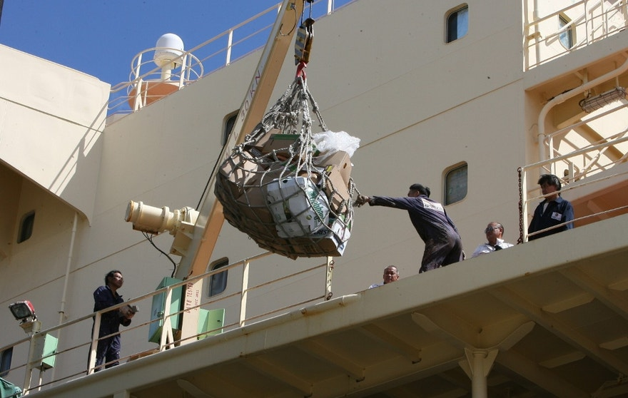CORRECTS TO NEWLEAD-Crew members pull supplies onto the deck of the Newlead Castellano. The cargo vessel has been stranded near Tybee Island for several months. The vessel was currently docked at Colonial Terminals in Savannah, Ga., for refueling and supplies on Tuesday, Aug. 9, 2016. A legal battle over debt has left a cargo ship and its 15-member crew stuck off the coast of Georgia for nearly four months. U.S. marshals seized the Newlead Castellano in mid-April after it sailed into Savannah with carrying sugar. A judge ordered the ship idled while creditors sued the ship's owner, saying they were owed $7.1 million. (AP Photo/Lewis M. Levine)