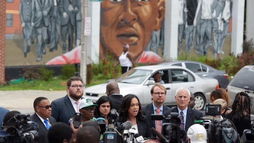 FILE- In this July 27, 2016, file photo, with a mural depicting Freddie Gray in the background, Baltimore State's Attorney Marilyn Mosby, center, speaks during a news conference after her office dropped remaining charges against the three Baltimore police officers who were still awaiting trial in Freddie Gray' death in Baltimore. Baltimore police officers routinely discriminate against blacks, repeatedly use excessive force and are not adequately held accountable for misconduct, according to a harshly critical Justice Department report being presented Wednesday, Aug. 10, 2016. (AP Photo/Steve Ruark, File)