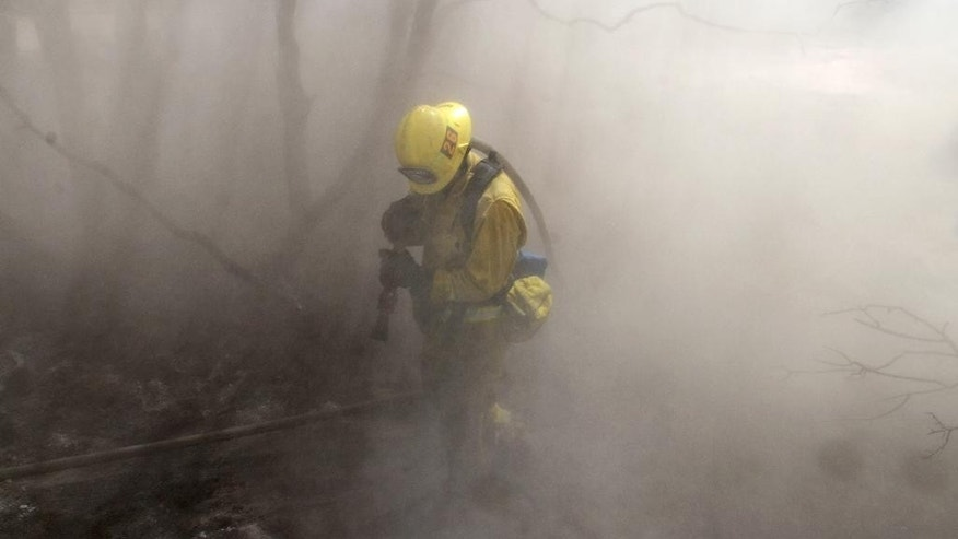 A San Bernardino County firefighter is shrouded in dust and smoke as handcrew members and bulldozer cleared smoldering debris from a wildfire in Hesperia, Calif., Tuesday. Aug. 9, 2016. (James Quigg/The Daily Press via AP)