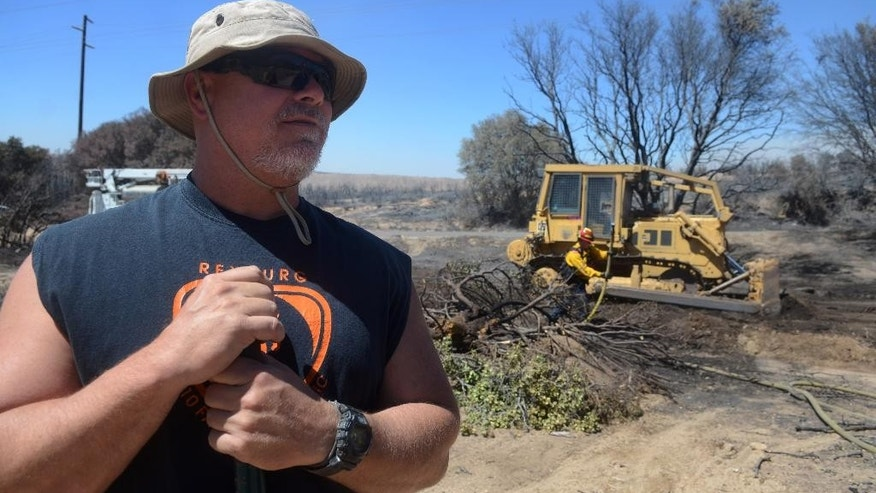 Summit Valley Resident Tom Flury watches San Bernardino County firefighters mop up the smoldering remains from a wildfire in Summit Valley, Calif., Tuesday. Aug. 9, 2016. (James Quigg/The Daily Press via AP)