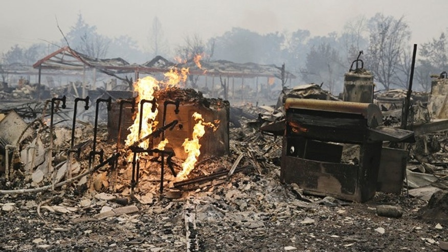 This Sunday, Sept. 13, 2015 file photo shows flames burn near gas lines at a destroyed apartment complex in Middletown, Calif.