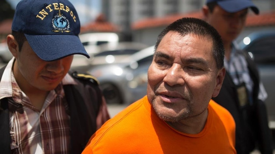 Santos Lopez Alonzo is escorted by Interpol agents after landing at the Air Force base in Guatemala City, Wednesday, Aug. 10, 2016. Lopez Alonzo, former Guatemalan soldier suspected of helping carry out a massacre of more than 160 people in 1982 during the country's civil war was deported from the United States on Wednesday after a court refused his plea to stay because he fears for his life. (AP Photo/Luis Soto)