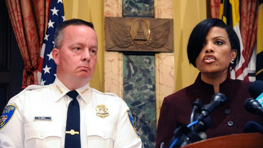 Police Commissioner Kevin Davis, left, listens as Baltimore Mayor Stephanie Rawlings-Blake speaks during a news conference at City Hall in response to a Justice Department report, Wednesday, Aug. 10, 2016 in Baltimore. The Justice Department and Baltimore police agreed to negotiate court-enforceable reforms after a scathing federal report released Wednesday criticized officers for using excessive force and routinely discriminating against blacks. (Kim Hairston/The Baltimore Sun via AP)