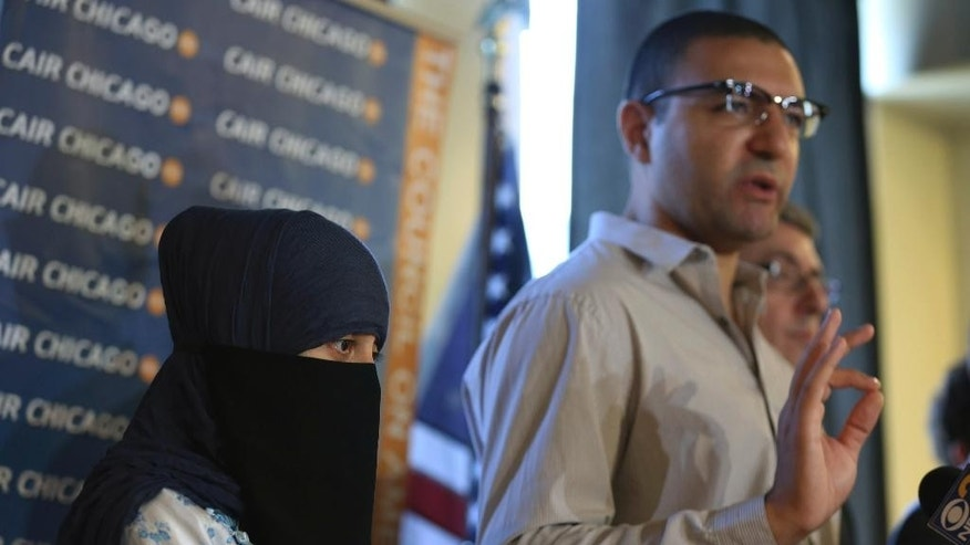 Itemid Al-Matar, left, listens as Hamed Rehab, right, Executive Director of CAIR-Chicago, speaks during a news conference, Thursday, Aug. 11, 2016 in Chicago. Itemid Al-Matar is suing Chicago police who falsely singled her out as a potential terrorist on July 4, 2015, as she left a subway station wearing a headscarf, face veil and carrying a backpack. (Abel Uribe/Chicago Tribune via AP)