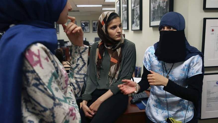 Siham Naser, left, and Lana Kashkeesh, center, both interns at CAIR-Chicago, listen to Itemid Al-Matar, at a news conference, Thursday, Aug. 11, 2016 in Chicago. Itemid Al-Matar is suing Chicago police who falsely singled her out as a potential terrorist on July 4, 2015, as she left a subway station wearing a headscarf, face veil and carrying a backpack. (Abel Uribe/Chicago Tribune via AP)
