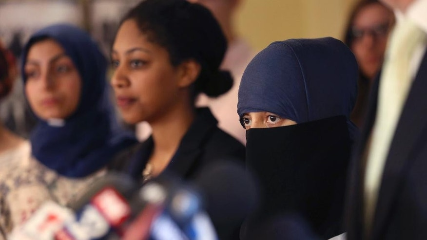 Itemid Al-Matar, right, stands by her lawyer Gregory Kulis, during a news conference, Thursday, Aug. 11, 2016 in Chicago. Itemid Al-Matar is suing Chicago police who falsely singled her out as a potential terrorist on July 4, 2015, as she left a subway station wearing a headscarf, face veil and carrying a backpack. (Abel Uribe/Chicago Tribune via AP)