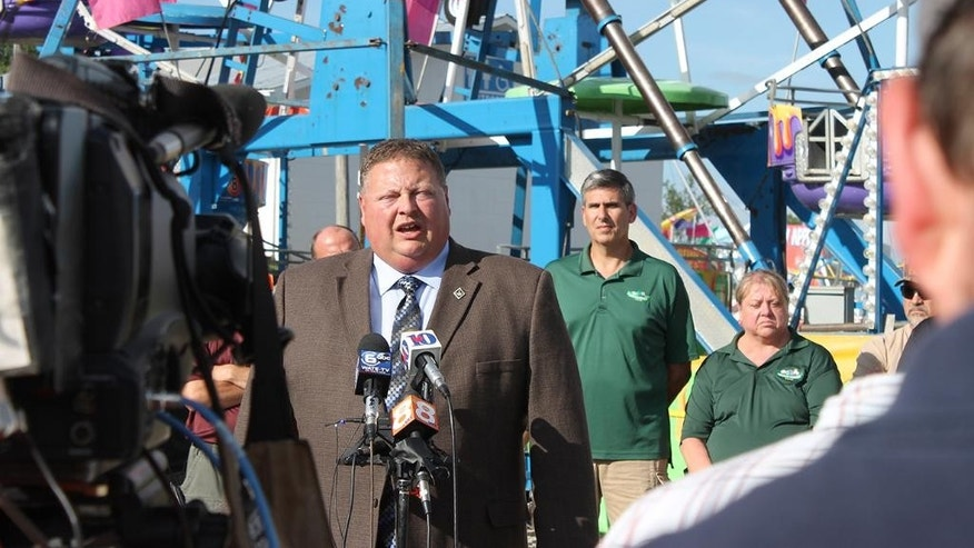 Greeneville Police Detective Capt. Tim Davis answers questions at the foot of the Ferris wheel at the Greene County Fair Tuesday, Aug. 9, 2016,  during a press conference. Members of the Greene County Fair Board of Directors stand behind him. Government investigators are still sorting out how a Ferris wheel seat flipped over at the county fair, sending three children plummeting 30 to 45 feet to the ground. (O.J. Early/Greeneville Sun via AP)