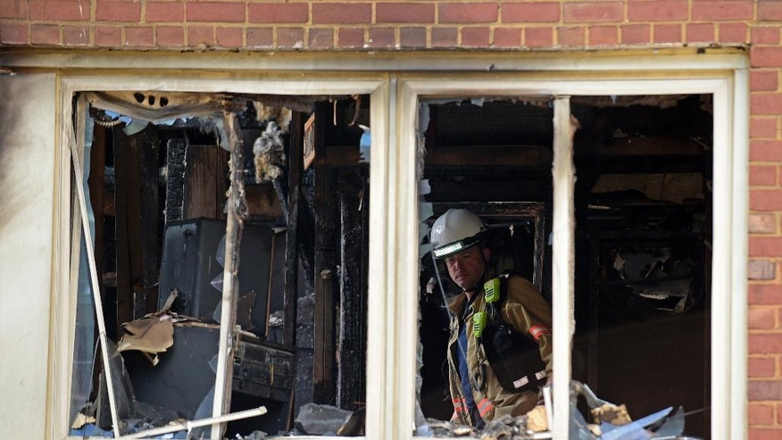 Emergency personnel investigate the inside of an apartment building following a fire in Silver Spring, Md., Thursday, Aug. 11, 2016. At least two people died and dozens, including three firefighters, were injured after an explosion and large fire at the apartment complex. (AP Photo/Susan Walsh)