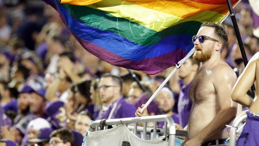 In this Sunday, July 31, 2016 photo, Major League soccer fans show solidarity with Pulse shooting victims by waving rainbow colored flags at a match in Orlando, Fla. In the aftermath of the Pulse nightclub shootings, the rainbow colors are appearing all over metro Orlando. (AP Photo/John Raoux)