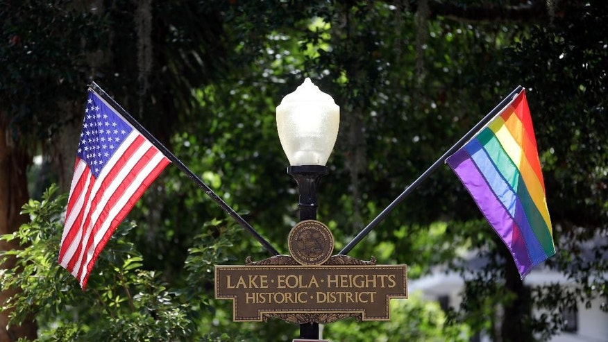 In this Monday, Aug. 1, 2016 photo, the rainbow flag flies along side of the American flag in the Lake Eola Heights neighborhood in Orlando, Fla. In the aftermath of the Pulse nightclub shootings, the rainbow colors are appearing all over metro Orlando. (AP Photo/John Raoux)