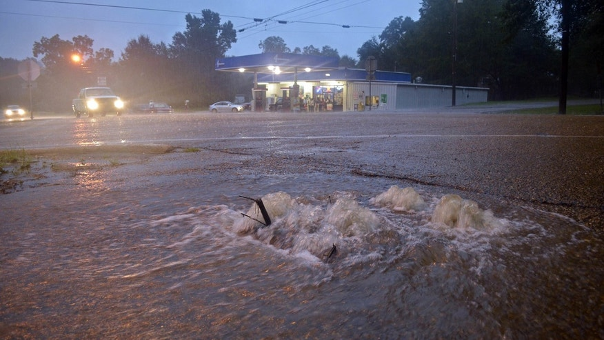 Aug. 12, 2016: Floodwaters surge from a crack in the parking lot on the corner of highways 584 and 51 in Osyka, Miss.