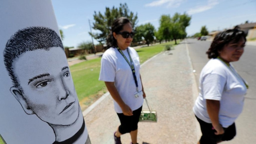 In this July 27, 2016 photo, neighborhood patrol officers Maribel Diaz Lopez, left, and Mario Ocampo walk Maryvale neighborhood streets in Phoenix to hand out an artist rendering of a suspected serial killer, as shown on the light pole, and block watch flyers. The serial killer has killed seven people since March and wounded two, sowing terror in a blue-collar swath of Phoenix. Police are pleading for tips to help them catch their suspect, but many residents never report crime because they are immigrants fearing deportation. (AP Photo/Matt York)